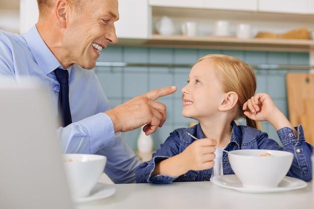 Aardige gelukkig opgetogen man lacht en kijkt naar zijn dochter