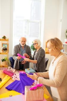 Aardige grijsharige vrouw die bij haar vriend staat terwijl ze hem advies geeft over het inpakken van cadeaus