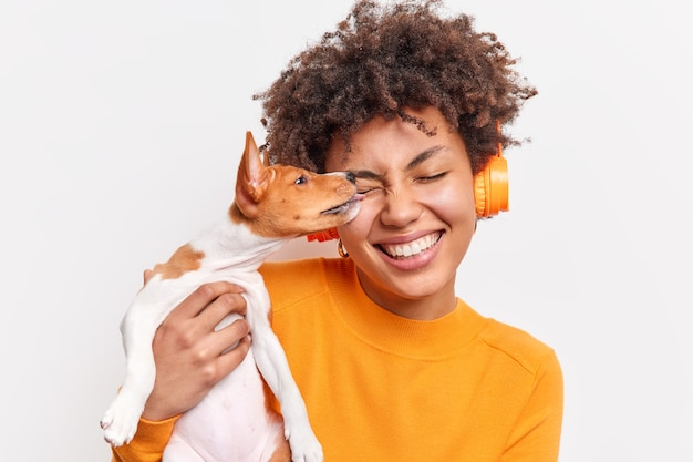 Aardige hond likt gezicht van vrouwelijke eigenaar met tederheid drukt liefde uit. gelukkige vrouw met krullend haar brengt tijd door met haar favoriete huisdier en luistert naar muziek in draadloze koptelefoons die op een witte muur zijn geïsoleerd