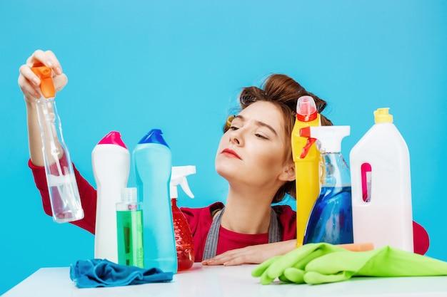 Aardige huisvrouw controleert informatie over fles en poseert met schoonmaakspullen
