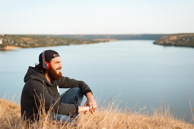 Aardige jonge bebaarde man zittend op het veld luisteren naar de muziek en glimlachen en wegkijken