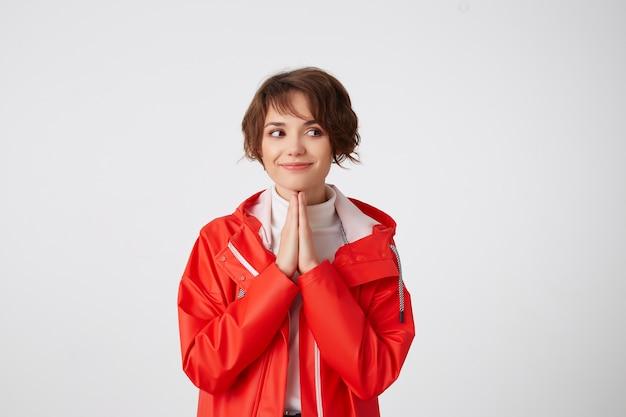Aardige jonge kortharige dame in witte golf en rode regenjas, met tot een kom gevormde handen die wegkijken, glimlachen en aan iets lekkers denken. staand.