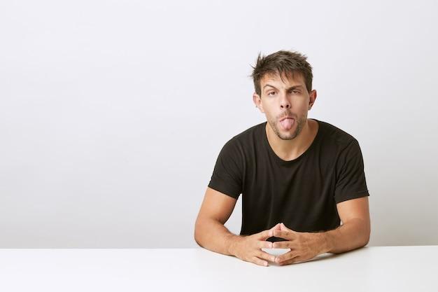 Aardige jonge man kijkt naar de camera en zijn tong uitsteekt. leunend op wit bureau, geïsoleerd op wit bureau. het dragen van een zwart t-shirt.