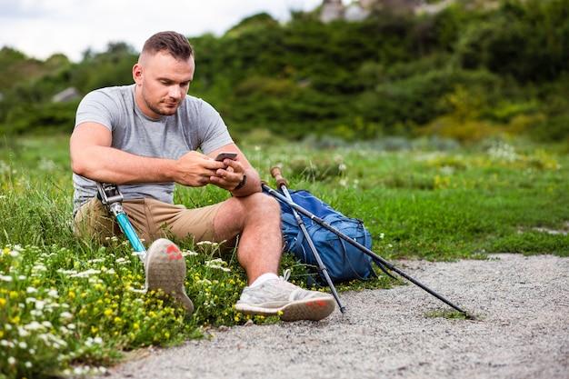 Aardige jonge man met een handicap zittend op het gras tijdens het gebruik van zijn smartphone
