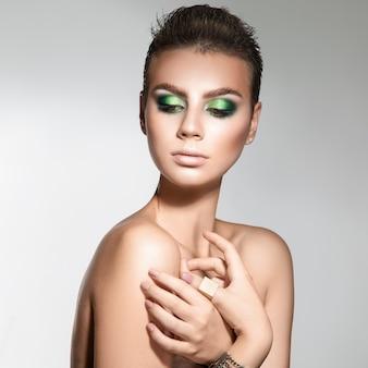 Aardige jonge volwassen vrouw met een gezonde huid en professionele make-up die naar de studio kijkt