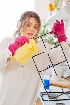 Aardige jonge vrouw die een detail van een gasfornuis vasthoudt terwijl ze het wil schoonmaken