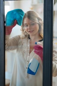 Aardige jonge vrouw die een reinigingsmiddel op het raam spuit terwijl ze het schoonmaakt