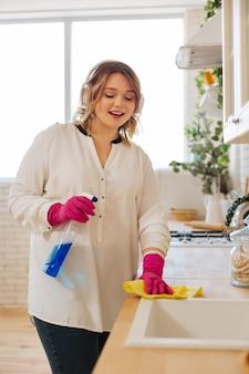 Aardige jonge vrouw die haar koptelefoon draagt terwijl ze naar muziek luistert tijdens het schoonmaken