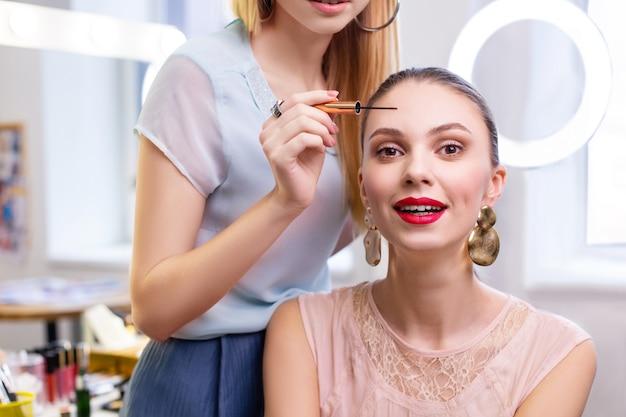 Aardige jonge vrouw die haar ogen schildert terwijl ze in de schoonheidssalon is