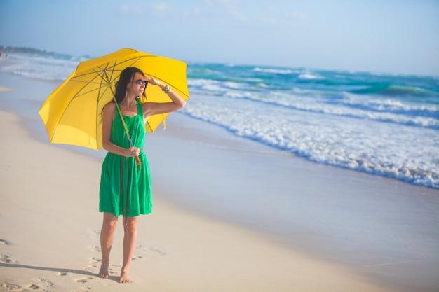 Aardige jonge vrouw die met gele paraplu alleen op het strand loopt