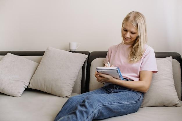 Aardige jonge vrouw die notities schrijft in een notitieboekje of dagboek, zittend op een bank in de woonkamer thuis