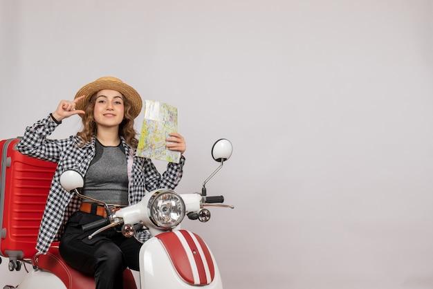 Aardige jonge vrouw op bromfiets met kaart op grijs