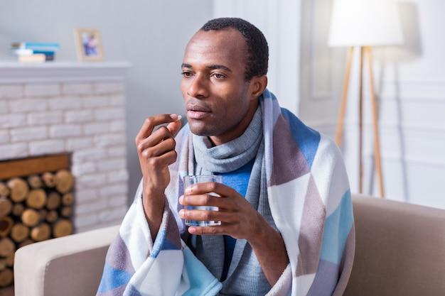 Aardige knappe bedachtzame man die een glas water vasthoudt en een pil neemt terwijl hij ziek is