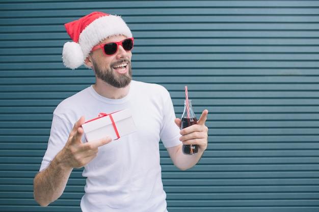 Aardige man staat en houdt aanwezig in één hand en fles cola in een andere. ook wijst de kerel met vinger. man draagt bril en hoed. geïsoleerd op gestreept