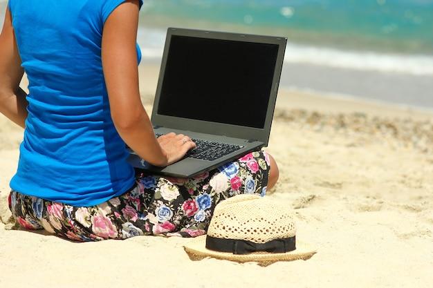 Aardige meid met laptop aan zee