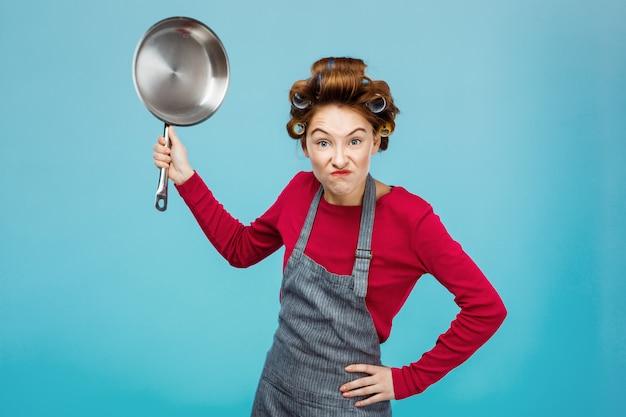Aardige meid probeert je bang te maken met een koekenpan