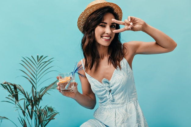 Aardige meid toont vredesteken, knipoogt en houdt water vast met sinaasappel. lachende vrouw met kort donker haar poseren in de buurt van kleine palmboom.