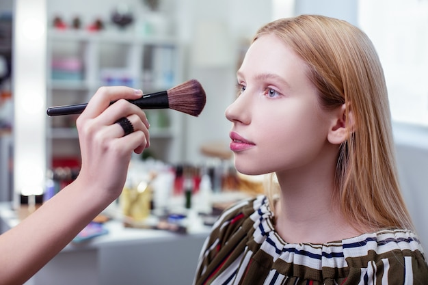Aardige mooie vrouw die in de schoonheidsstudio zit terwijl haar make-up wordt gedaan