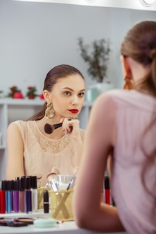 Aardige mooie vrouw die in de spiegel kijkt terwijl ze aan haar uiterlijk denkt Premium Foto
