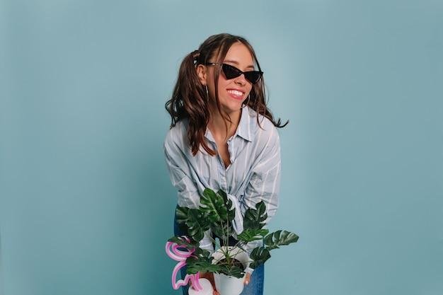 Aardige mooie vrouw met donker haar, gekleed in blauw shirt, bloempot vast te houden en lachend, poseren tegen een blauwe muur
