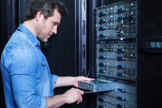 Aardige professionele mannelijke technicus die een bladeserver vasthoudt en deze in het serverrek installeert terwijl hij zijn werk doet