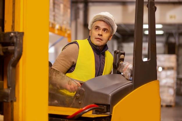 Aardige serieuze man die de voertuigmachine bestuurt tijdens het opslaan van pakketten