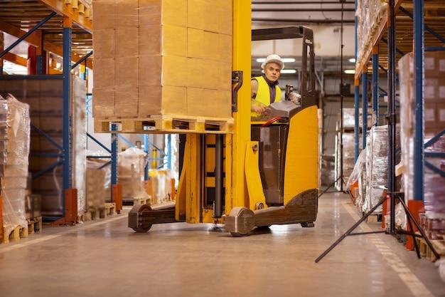 Aardige serieuze man met dozen tijdens het besturen van een speciaal machinevoertuig