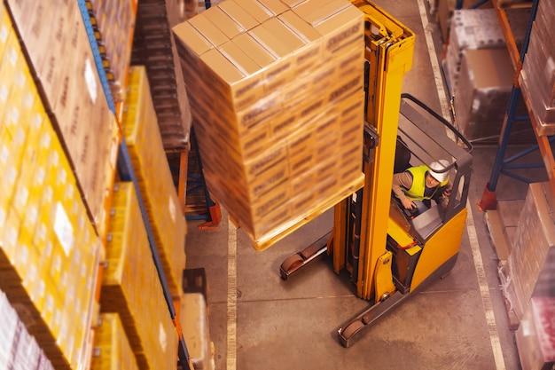 Aardige slimme man die het machinevoertuig gebruikt terwijl hij dozen op de opslagplank zet
