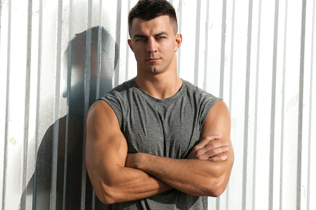 Aardige spiermens. portret van fitness atleet knappe man poseren buiten met gekruiste armen