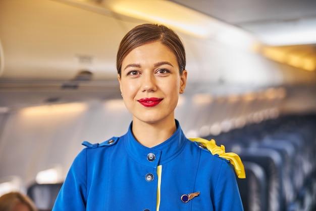 Aardige stewardess die met een glimlach naar de camera kijkt