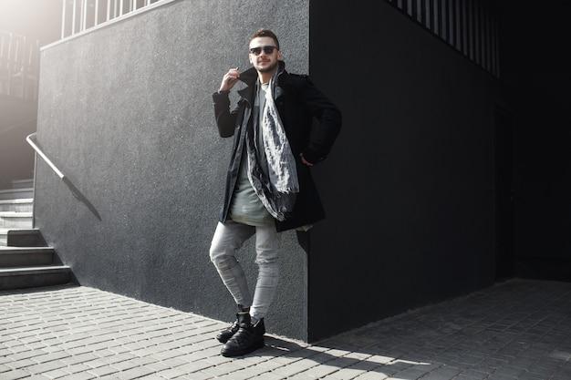 Aardige vent in stijlvolle kleding die buiten staat, leunend tegen de muur.
