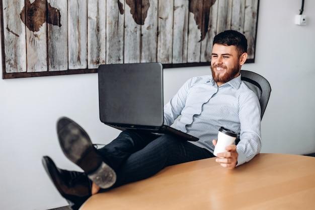 Aardige vent met een baard die aan een tafel zit, zijn voeten op de tafel zet, koffie drinkt en op een computer werkt
