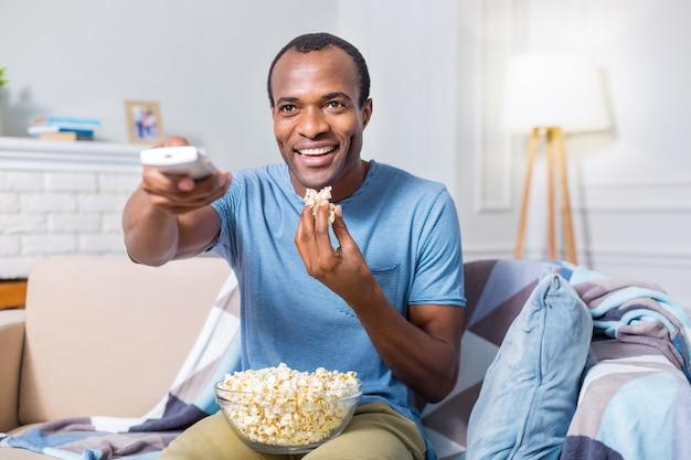 Aardige, vrolijke, vrolijke man die lacht en tv kijkt terwijl hij een kom met popcorn vasthoudt
