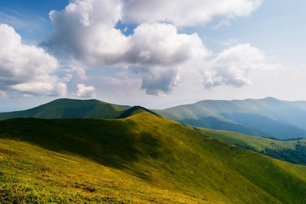 Aardlandschap met wolken boven bergen.