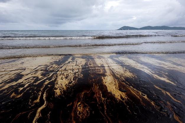 Aardolielekkage vermengd met andere chemische stoffen op zee- en zandoppervlak.