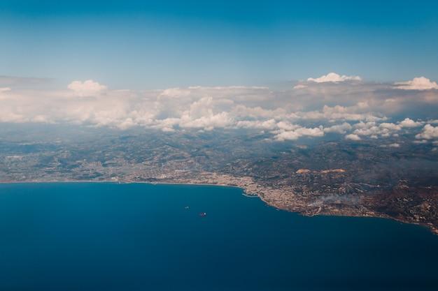 Aardoppervlak, zeekust en wolken, uitzicht vanuit het vliegtuig