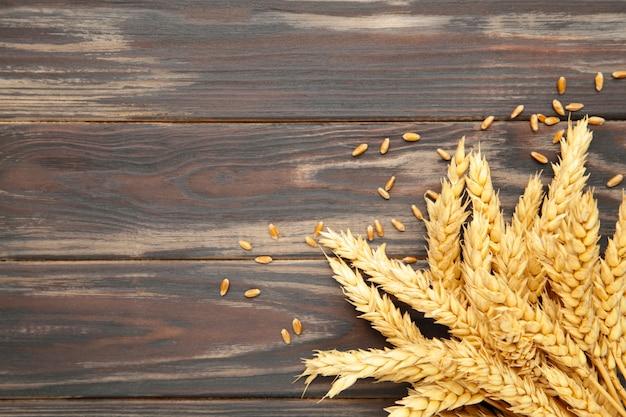 Aartjes van tarwe op bruine achtergrond. bovenaanzicht