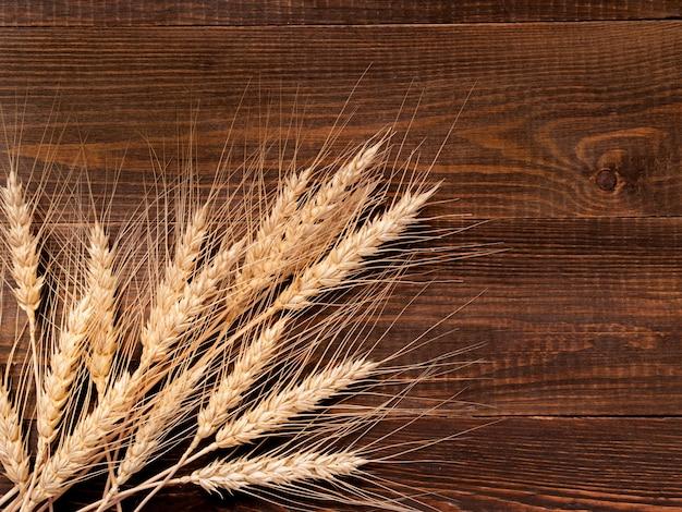 Aartjes van tarwe op houten achtergrond