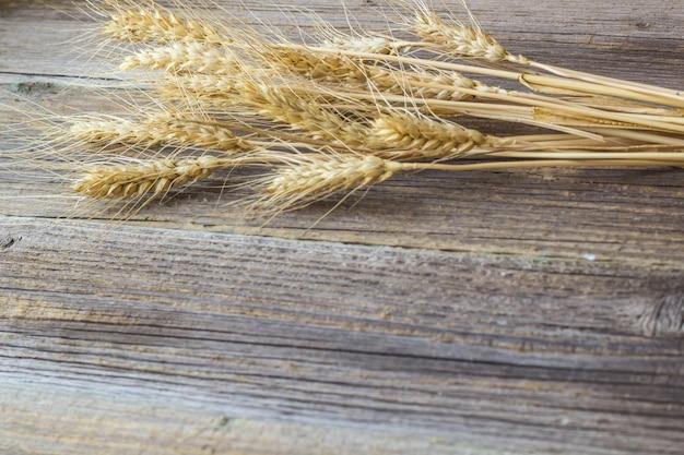 Aartjes van tarwe op natuurlijke oude houten tafel.