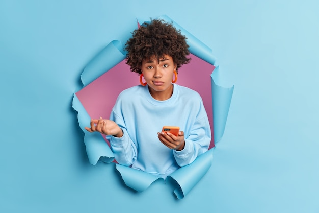 Aarzelend niet wetende afro-amerikaanse vrouw weet niet waarom haar telefoon niet werkt, lost het probleem niet op met moderne gadget ziet er geen idee van aan de voorkant gekleed nonchalant gekleed in gescheurde blauwe papieren muur