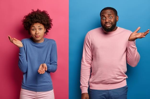 Aarzelend ondervraagde zwarte vrouw en man halen hun schouders op met onnozele uitdrukkingen, hebben geen suggesties, spreiden de handpalmen met twijfel, nemen een beslissing