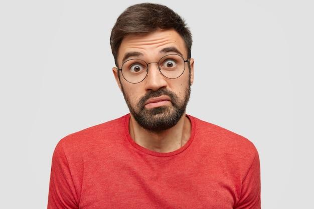 Aarzelende bebaarde jongeman hipster kijkt twijfelachtig en verrassend, draagt rode kleren, krijgt onverwacht voorstel