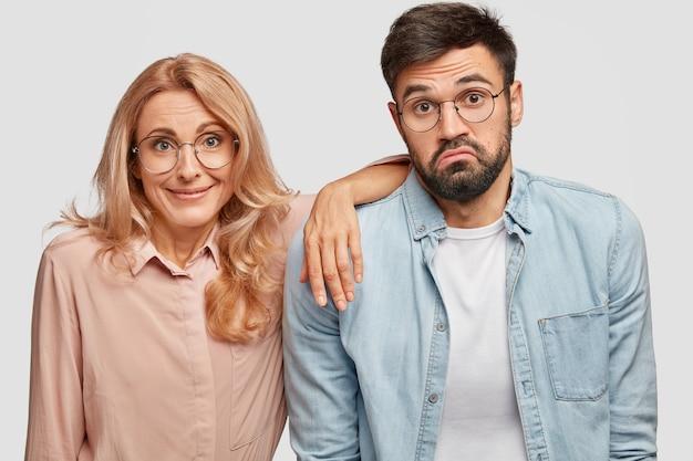 Aarzelende bebaarde man staat in de buurt van zijn blonde vrouw collega die tevreden uitdrukking heeft