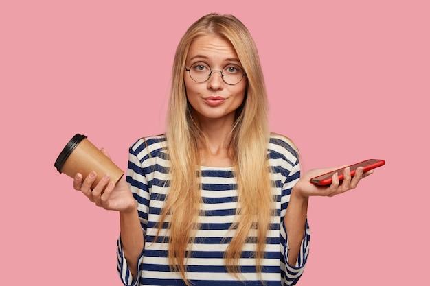 Aarzelende blonde student die tegen de roze muur poseert