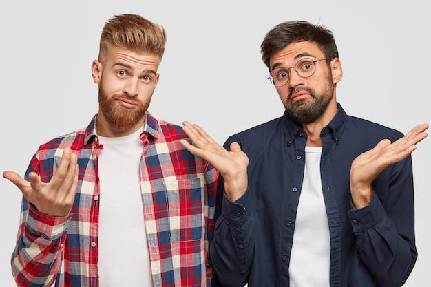 Aarzelende broers met een baard vouwen elkaars handen vol verwarring en verbijstering, staan naast elkaar, voelen zich geen idee