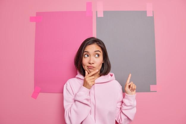 Aarzelende brunette jonge aziatische vrouw houdt kin portemonnees lippen heeft twijfelachtige gezichtsuitdrukking wijst naar boven toont promo vooruit top verkoop promotie draagt casual hoodie poses tegen roze muur