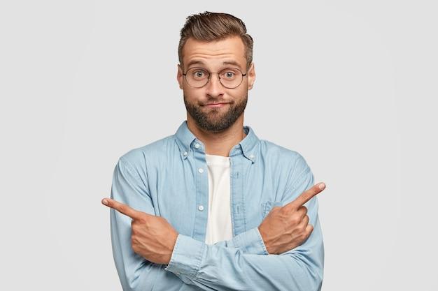 Aarzelende en onwetende man steekt handen over de borst, wijst met wijsvingers in verschillende kanten of richtingen