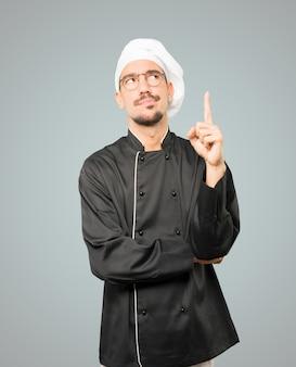 Aarzelende jonge chef-kok die met zijn vinger omhoog wijst