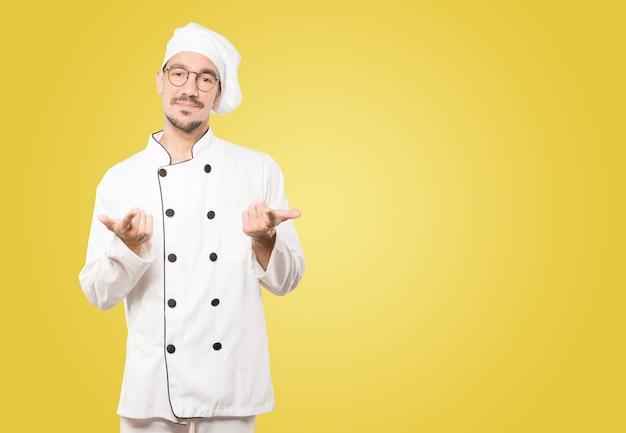 Aarzelende jonge chef-kok die op je wijst met zijn vinger