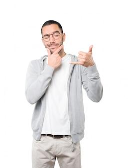 Aarzelende jonge man die een gebaar maakt om met de hand te roepen